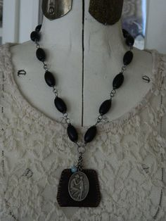 This necklace is composed with a vintage leather Scapular, a vintage medal from Belgium, and vintage wood rosary beads. The vintage depicts a woman and child. The back of the medal reads, Ceuvre Nationale des Orphelins de la Guerre La Fleur de LOrphelin Ceuvre de Dotatio. Although I am unable to totally translate this medal, I can translate the word Orphelin as orphan, and Guerre meaning war. So, my best guess is that this medal has to do with orphans of a war. This art medal of the woman…