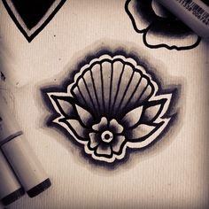 Black and white old school shell and flower. Love the way the colour fades out and makes the tattoo pop so much more!