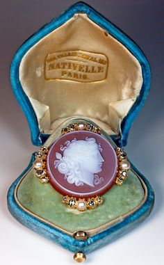 Victorian Era Cameo Brooch, French, circa 1870: a finely carved carnelian cameo of Dionysus, the Greco Roman god of wine making and fertility, set in 18K gold bezel embellished with half pearls and rose cut diamonds Marked with French eagle-shaped assay mark The cameo brooch comes in its original blue velvet retailer's case stamped in gold. 165 PALAIS ROYAL NATIVELLE PARIS.