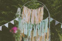 Une arche de cérémonie faite avec des bande de tissu et des fanions.