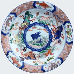 A Chinese famille verte dish decorated with a carp. kangxi period. China. Asia. Decorated in the famille verte palette to the interior with three buddhistic lions frolicking on rocky promontories alternating with three horses prancing on stylized circular waves
