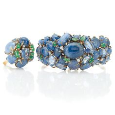 Gold, Sapphire, Cabochon Sapphire, Emerald and Diamond Cuff Bangle Bracelet and Ring, Seaman Schepps  14 kt., the hinged bangle centering a domed cluster of 25 oval cabochon sapphires, 5 cushion-shaped sapphires, and 7 rectangular-cut emeralds, accented by 5 round diamonds, signed Seaman Schepps, the dome ring centering one cushion-shaped sapphire, flanked by 4 rectangular-cut emeralds, encircled by 7 round and oval cabochon sapphires, set with 9 small round diamonds, circa 1940