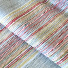 A beautiful woven striped upholstery fabric in soft grey with coral red, shell pink, sea blue, citrine yellow green and white.This durable fabric is suitable fo