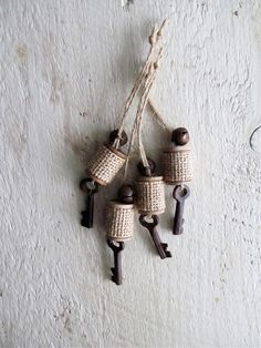 Adorable ornaments made from wood thread spools. Strips of burlap wrap around each spool, a rusty jingle bell adorns the top and a rusty skeleton key