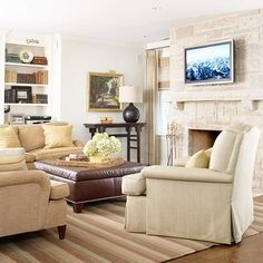 A large stone fireplace makes this neutral living room a comfortable place to relax. More living room design ideas: http://www.bhg.com/rooms/living-room/makeovers/living-room-decorating-ideas/?socsrc=bhgpin070212#page=5