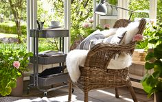 A wicker chair in an enclosed balcony with a wheeled storage unit and potted plants with a view of a garden in the background. #IKEA