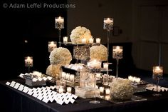 what we're considering doing for the escort table --- with some of our colors rather than all white  Multi level tablescape with white floral spheres,plexyglass shelves, floating candles, glass block #black and white wedding #floating candles #contemporary design