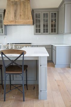 grey farmhouse kitchen . custom barnwood hood. open concept