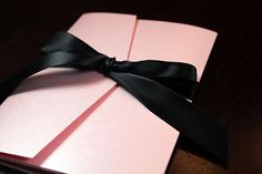 Elegant pink and purple letterpress invitation in pocketfold with black satin ribbon
