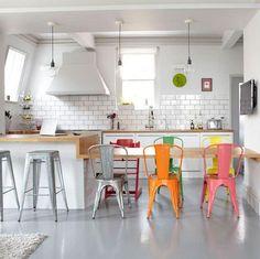 Sillas de diferentes colores en la cocina blanca.