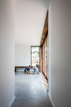 """Hallway and Concrete Floor In the new sitting room, the architects opted for timber-framed windows and doors. """"In this space the fixed joinery elements invert the original material strategy of the house,"""" they write. Photo 11 of 15 in An Architect's 1958 Midcentury in Tasmania Gets a Graceful Renovation"""
