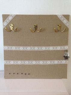 Tableau créer pour ranger les bijoux. Planche de médium recouvert de tissus, orné de dentelle et de 3 portes manteaux chiné sur une foire à tout. La dentelle est parfaite pour ranger les boucles d'oreilles, les portes manteaux , pour les colliers. Quelques clous sur le bas pour les bracelets.