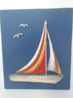 This is a very cool, unique string art picture of a sailboat and seagulls. The sails consist of four different colored layers, and the boat is a