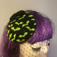 Perfect for any spooky gal (or for Halloween), Bijou Vixens custom black and neon green bat fascinator cocktail hat. With black crystals, black ribbon roses, and birdcage veil.