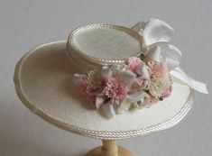 This is a beautiful ivory silk 1/12th scale dollshouse silk hat. The hat is made from pure ivory silk trimmed with ivory lacet and is