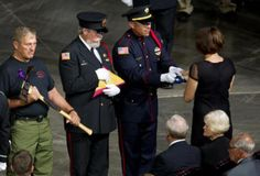 A flag is presented to Juliann Ashcraft, widow of fallen firefighter Andrew Ashcraft, during the memorial service at TIm's Toyota Center in Prescott Valley, Ariz. for the 19 Granite Mountain Hotshots killed fighting the Yarnell Hill Fire on June 30, 2013.