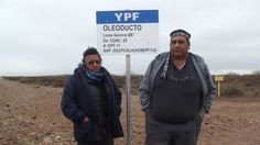 Josifa and Albino Campo stand in front of a sign for a YPF oil pipeline