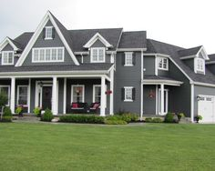 Dark gray siding, dark shutters, white trim.