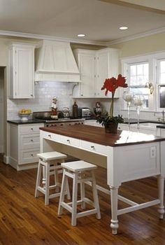 This kitchen layout and general style is great.  Love the island table, gives a much more open look to the room. The rangehood is too ornate for my taste, prob would have one built in to matching overhead cupboards.