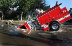 A 22-ton Los Angeles Fire Department fire truck protrudes from a sinkhole on September 8, 2009 in the Valley Village neighborhood of Los Angeles, California. Firefighters were dispatched to investigate an early morning call about flooding on a residential street when the driver saw a large amount of water in the darkness. The driver was backing up when the truck fell into the sinkhole, apparently caused by a broken 6-inch cast iron pipe.