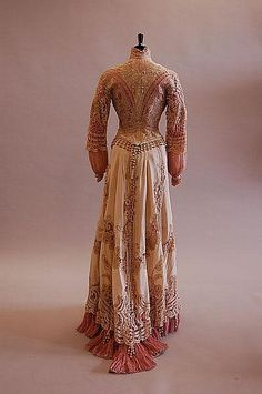 : A tapelace pink and ivory silk summer gown, circa 1900, the bodice and skirt with elaborate tasselled trim, bust 82cm, 32in, waist 61cm, 24in
