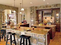The kitchen of this Idea House exudes a polished look while maintaining a sense of warmth. Pine floors add richness, while the cabinetry displays a smooth walnut finish. Granite countertops inject more luster. To make meal prep easier, the center island features a vegetable sink. (Photo: Photo: Van Chaplin; Stylist: Lisa Powell)