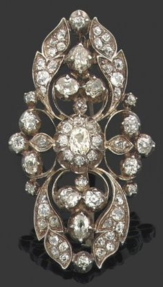 A Belle Époque silver and diamond pendant-brooch of foliate design.