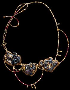 """""""Gaurdians of the Treasure"""", this piece combines sculpted elements, accented with pearl, boulder opal, garnet, and faceted ruby beads. They are linked together with 14 k. goldfilled wire and strung on 24k. gold-covered flexible steel cable with glass beads, electroplated 23 k. gold beads and pearl."""