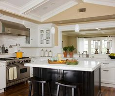 Tan + White + Black - Classic in every way, this traditional-style kitchen sets off its elegant white cabinets and coffered ceiling with warm tan walls. A black-painted island anchors the space. White backsplash tiles and marble countertops create continuity throughout. Wire door inserts add country-style texture in the upper cabinets that flank the range hood