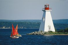 * Small Sailboats Racing past a Lighthouse in Nova Scotia, Canada