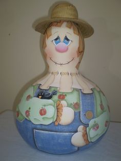 Espantalho pintado a mão em cabaça, com chapéu de palha e botões em biscuit.