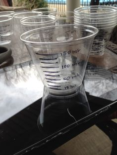 """Beakers"" clear plastic cups and wrote on with sharpie, to hold art supplies in ""lab"" room"