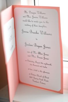 Invitations made by the bride- coral cardstock folded in half, a pocket made on the left side, and the white cards on the left side pull out and have directions, RSVP, and reception information