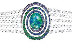 BOUCHERON. Aiguebelle bracelet, set with an oval opal cabochon and rock crystal beads, set with emeralds, blue and purple sapphires and diamonds, on white gold.