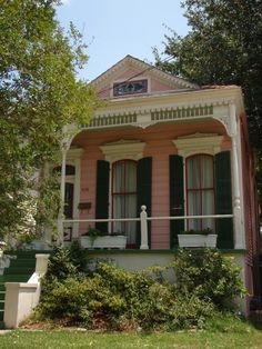 New Orleans pink shotgun house- love the moulding over the windows with the shutters on the porch.