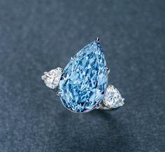 A MAGNIFICENT 8.26 CARAT FANCY INTENSE BLUE DIAMOND AND DIAMOND RING. Set with a pear-shaped fancy intense blue Type IIb diamond weighing 8.26 carats, flanked on either side by pear-shaped diamonds weighing 0.90 (D/VS1) and 0.98 carats (D/SI1), mounted in platinum. Estimate Upon Request // SOLD PRICE USD 15,406,080. GIA / Natural Fancy Intense Blue color, VS2 clarity, with excellent polish [POLY AUCTION HK - Magnificent Jewels - 2 OCT. 2017] #POLYAuction #FancyIntenseBlue #Diamond #IIbType