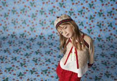 Junior Look 4 from the new Gucci Children's Cruise Collection. Featuring a beige crochet cardigan with signature Web details, over a white floral embroidered shirt, and a red floral lace skirt.