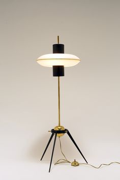 Stilnovo (attributed to), Italy 1950's Lamp with black varnished metal tripod foot. A slightly tilting shade is fixed towards the top of the stem, that consists of two white opaline glass discs, shaped like a flying saucer, and which contains three bulbs. The theme of 'space' is clearly referred to in this example and it inspired many lamps designed in the 1950's and 1960's.