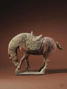 Tang dynasty A rare painted pottery figure of a horse nuzzling its leg