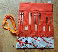 Awesome tutorial for knitting needle roll (pockets at three different heights for straight needles, DPNs and circular needles). Main fabric on the outside, bottom pockets and top fold, with the remainder in contrasting lining fabric, sandwiched with fusible fleece and tied with grosgrain ribbon.