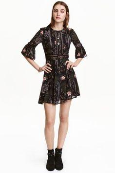 Jurk van chiffon en kant: Een korte jurk van crêpechiffon met ingezette kanten biezen. De jurk heeft driekwart mouwen met een volant onderaan, een splitje met een knoop in de nek, een naad in de taille en een uitlopende rok. Gevoerd met tricot.