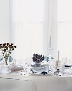 """Brides.com: . ice land.  A magically white, minimalist table gains organic richness from spherical flora (like scabiosa seed heads, far left, and brunia, center). ROCK CRYSTALS (above and opposite) from $95 each, ABC Carpet & Home (212) 473-3000 SNOWFLAKE (right) Mica $3.99/set of six, jamaligarden.com TALL CANDLESTICK (above and opposite) """"Festivo"""" $48, RED-WINE GLASSES (above and opposite) """"Ultima Thule"""" $36/pair, WHISKEY-SOUR GLASS (used as vase on left, opposite) """"Ultima Thule"""" $30/pair…"""