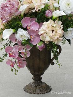Faux floral design with peonies, hydrangeas and orchids in urn
