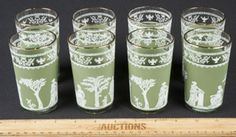 BEAUTIFUL SET OF 8 JUICE/DRINKING GLASSES IN THE GRECIAN HELLENIC PATTERN IN A WEDGWOOD GREEN BY JANETTE. BRING ELEGANCE TO YOUR TABLE WITH THESE GORGEOUS GLASSES IN 22K GOLD TRIM. THEY ARE IN EXCELLENT CONDITION. MEASURE 4 IN. TALL.