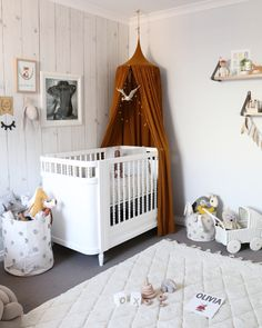 Gender neutral nursery room. Gold mustard canopy with wood look wall paper. Woodlands meets bohemian theme @misskyreeloves Liapela.com