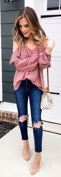 red and white polka-dot cold-shoulder shirt with blue denim jeans.