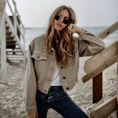 Oversized beige jacket over white tee and denim jeans.