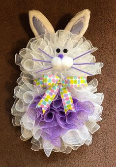 Handmade Spring/Easter Deco Mesh Bunny Wreath Made with a wire wreath, chenille stems, deco mesh, ribbon, bunny ears and googly eyes. Deco Mesh includes: White for Body & Purple for Belly Ribbon includes: Multicolor Easter Egg Print Nose/cheeks are made with Pom poms. Whiskers