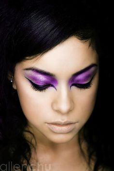 Pale coverup.  Super bright purp shadow. Cover whole lid w/ light wash. Layer shadow til dark from inner corner to middle lid, keep ends sightly layered but not as bright. Blk liq liner; line thickly in usual places, then feather in the outside corner like a cat eye, then work on the inner corner, connecting line to move downwards