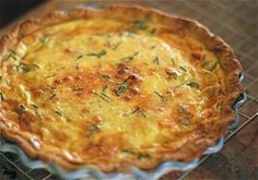BACON & GREEN CHILI QUICHE - 8 strips bacon, cooked and roughly chopped 1 (4-ounce) can green chilis, drained and finely chopped 4 scallions, chopped 1 ½ cups shredded sharp cheddar cheese ½ cup shredded Monterey Jack 1 ¼ cups half and half 4 eggs 1 large pinch kosher salt ½ teaspoon freshly cracked black pepper 1 teaspoon finely chopped chives 1 pie crust